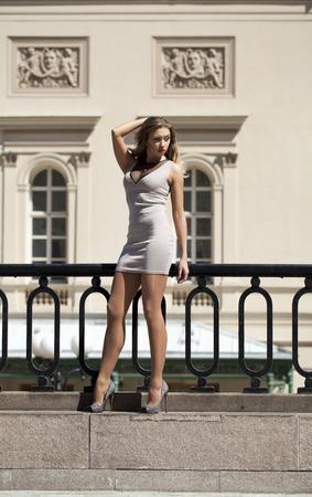 vestido corto: Retrato en pleno crecimiento, joven y bella mujer rubia en vestido corto de color beige posando al aire libre en un d�a soleado
