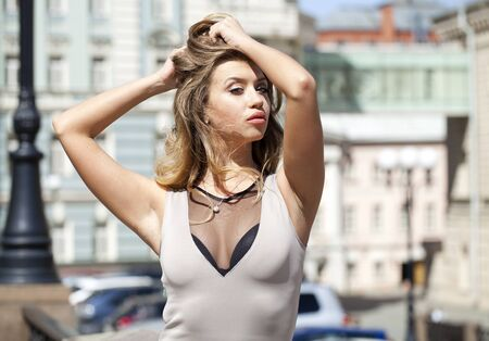 short dress: Young beautiful blonde woman in beige short dress posing outdoors in sunny weather