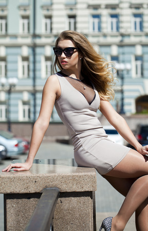 full height: Portrait in full growth, Young beautiful blonde woman in beige short dress posing outdoors in sunny weather
