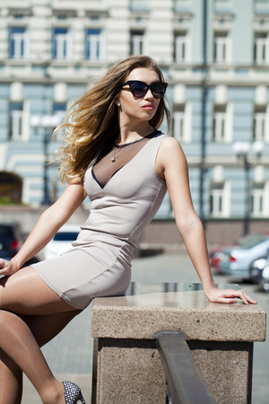 Portrait in full growth, Young beautiful blonde woman in beige short dress posing outdoors in sunny weather photo