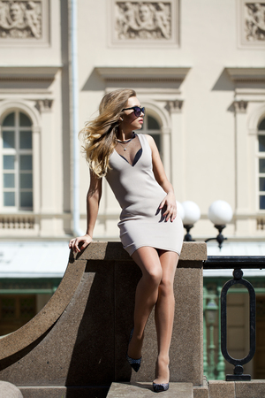 short dress: Portrait in full growth, Young beautiful blonde woman in beige short dress posing outdoors in sunny weather