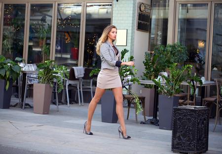 Jonge mooie zakelijke blonde vrouw in een beige jurk en een sexy stijlvolle jas loopt op straat