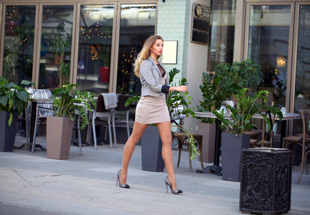 Young beautiful business blonde woman in a beige dress and sexy stylish jacket walks on the street