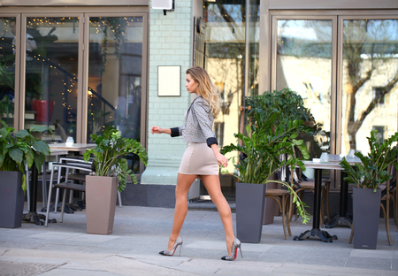 away: Young beautiful business blonde woman in a beige dress and sexy stylish jacket walks on the street