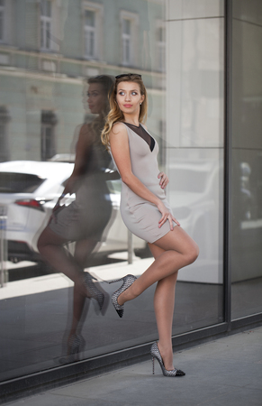 wall mirror: Portrait in full growth, Young beautiful blonde woman in beige short dress posing against a background of a wall mirror
