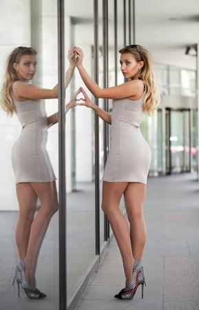 vestido corto: Retrato en pleno crecimiento, joven y bella mujer rubia en vestido corto de color beige, posando sobre un fondo de un espejo de pared