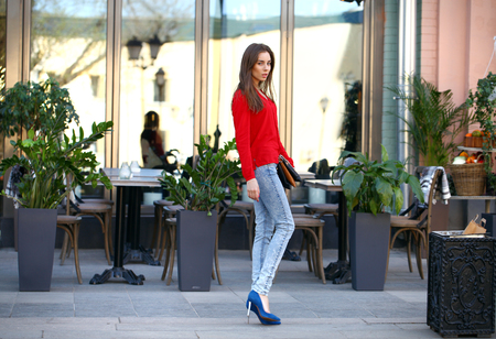 girl in full growth: Portrait in full growth the young beautiful girl in blue jeans and red shirt on the background of summer street