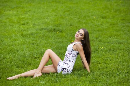 sitting pretty: Sexy brunette woman in short dress sitting on green grass
