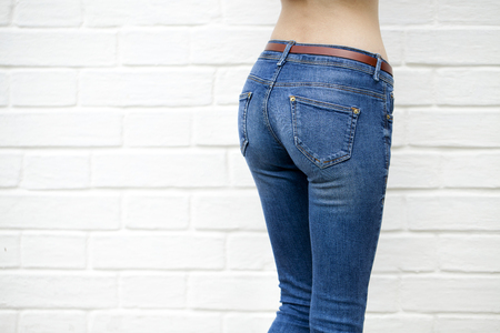 ass jeans: Part of the body, blue jeans for women on the background wall against the white brick white wall