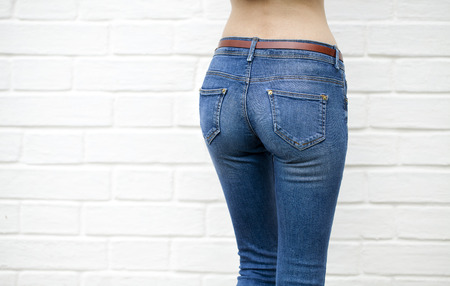 belly button girl: Part of the body, blue jeans for women on the background wall against the white brick white wall
