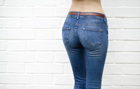 ombligo: Parte del cuerpo, pantalones de mezclilla de las mujeres en la pared de fondo contra la pared blanca de ladrillo blanco Foto de archivo
