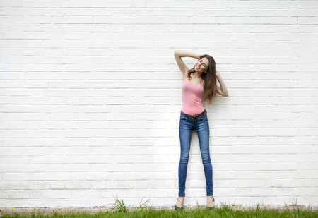 jeans: Full length portrait of a beautiful woman in blue jeans against a white brick wall