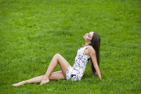 grass beautiful: Sexy brunette woman in short dress sitting on green grass