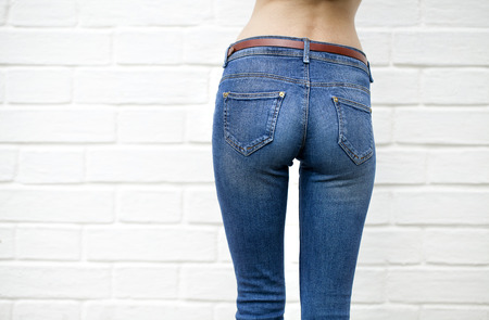 Part of the body, blue jeans for women on the background wall against the white brick white wall