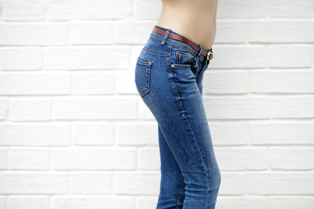 bare waist: Part of the body, blue jeans for women on the background wall against the white brick white wall
