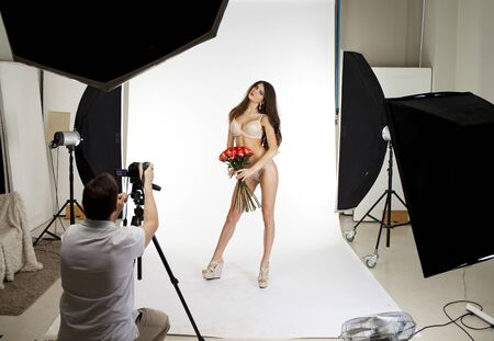 photographers: Working conditions in the studio, the photographer photographs the professional model