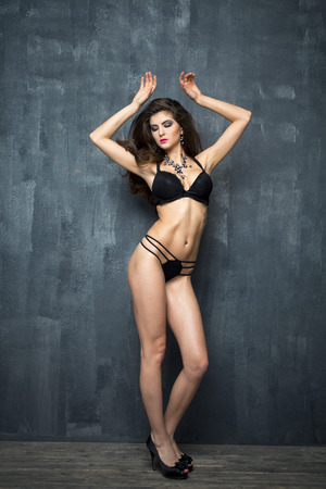 sexy underwear: Portrait of sexy brunette woman in black underwear on a dark wall Stock Photo