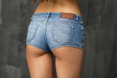 Female body part denim jeans shorts against the dark wall