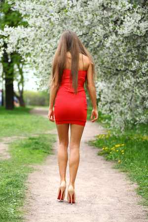 red dress: Beautiful woman in red dress walking spring park Stock Photo