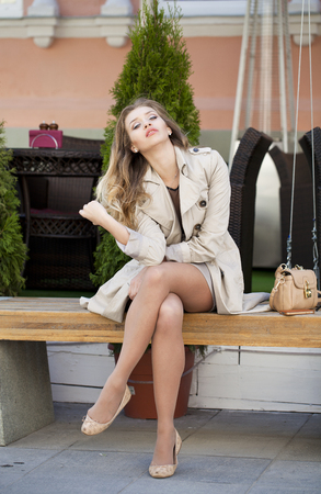 full height: Young beautiful blonde woman in a beige coat sitting on a bench in the street