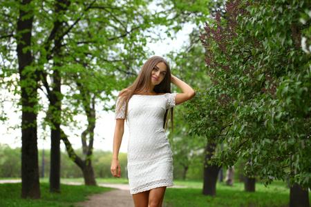 vestido blanco: Hermosa mujer morena con vestido blanco caminando en el parque de la primavera Foto de archivo