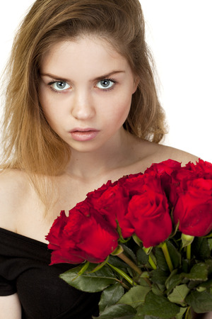 Portrait of a young beautiful blonde girl with a bouquet of red roses, isolated on white background photo