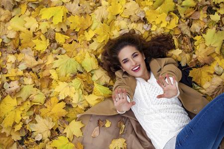 femme brune: Belle jeune fille en jeans bleu couché sur les feuilles jaunes, vue de dessus, dans le parc de l'automne