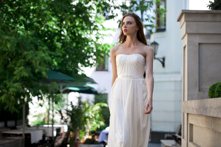 pose sensual: Portrait of beautiful model woman in wearing white dress posing summer street