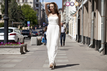 beautiful dress: Full length portrait of beautiful model woman walking in white dress in summer street