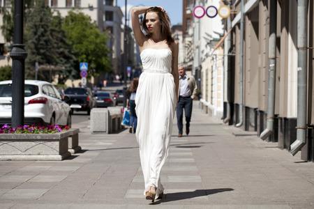 long: Full length portrait of beautiful model woman walking in white dress in summer street