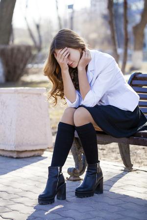 fille pleure: Belle jeune écolière blonde assise sur un banc, rue de printemps