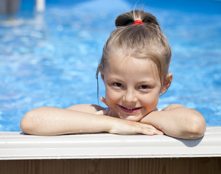 niños rubios: Niña feliz en bikini azul piscina