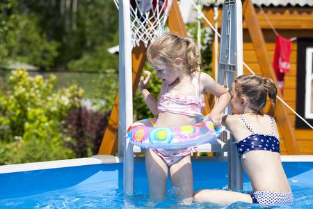 6 years girl: Two Happy sisters in bikini swimming pool