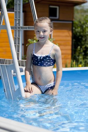 russian girls: Happy little Girl in blue bikini swimming pool Stock Photo