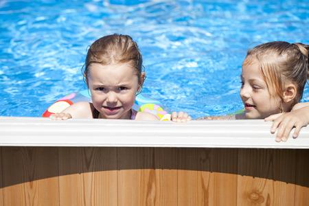 little girl child: Two Happy sisters in bikini swimming pool