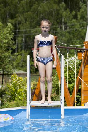 6 years girl: Happy little Girl in blue bikini swimming pool Stock Photo