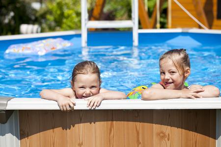 bikini wear: Two Happy sisters in bikini swimming pool