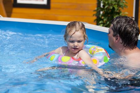 bikini wear: Little girl in bikini bathing in the pool with his father