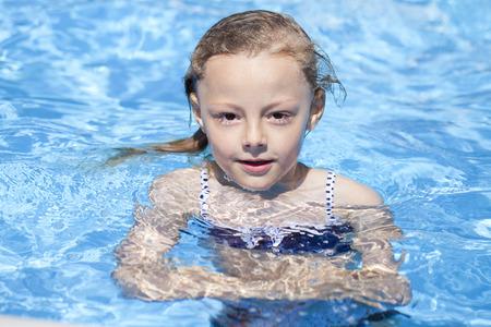 one child: Happy little Girl in blue bikini swimming pool Stock Photo