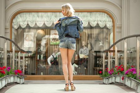 rubia: Retrato en pleno crecimiento de la joven rubia en una chaqueta azul y pantalones vaqueros cortos en contra de la tienda de escaparate telón de fondo