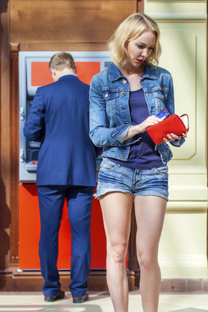 automated teller: Blonde lady using an automated teller machine. Woman withdrawing money or checking account balance