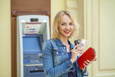 cash slips: Blonde lady using an automated teller machine. Woman withdrawing money or checking account balance