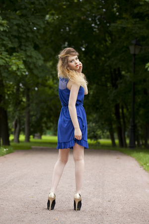 ass standing: Portrait in full growth, attractive young blonde woman in blue dress walking in summer park