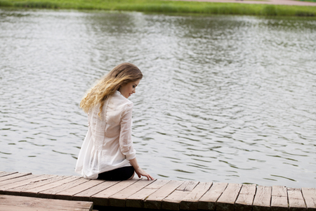 tunic: Young beautiful blonde woman in a white tunic sits on a wooden pier on the lake Stock Photo