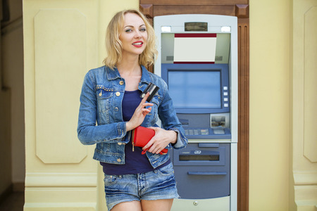 checking account: Blonde lady using an automated teller machine. Woman withdrawing money or checking account balance