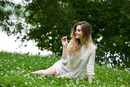 vestido blanco: La mujer rubia joven atractiva en vestido blanco sentado en la hierba verde en el parque de verano