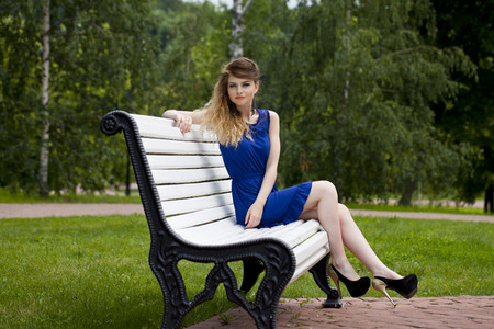 blue dress: Young beautiful blonde girl in blue dress sitting on a bench in summer park