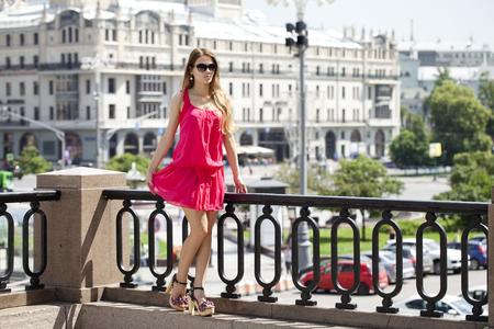 vestido corto: Young beautiful blonde woman in red short dress posing outdoors in sunny weather Foto de archivo