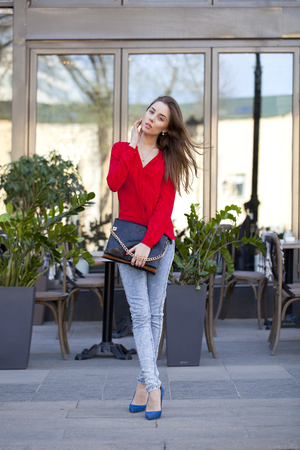 red shirt: Portrait in full growth the young beautiful girl in blue jeans and red shirt on the background of summer street