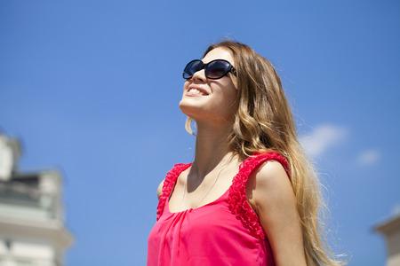 carita feliz: Joven y bella mujer rubia con gafas de sol, contra el cielo azul en un d�a soleado